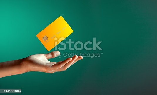 Close up female hand holds levitating template mockup Bank credit card with online service isolated on green background. High quality photo