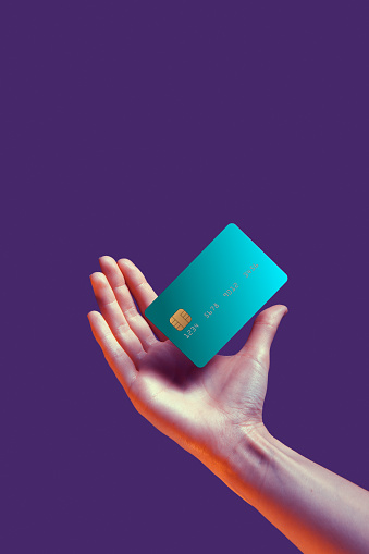 Close up female hand holds levitating template mockup Bank credit card with online service isolated on violet background. High quality photo