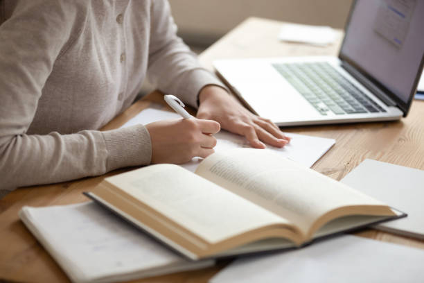 Close up female student writing down notes from opened textbook. Close up female student sitting at desk, writing down notes from opened textbook and laptop. Young girl preparing for university session, exams, doing homework, paperwork, writing coursework or essay. literature stock pictures, royalty-free photos & images