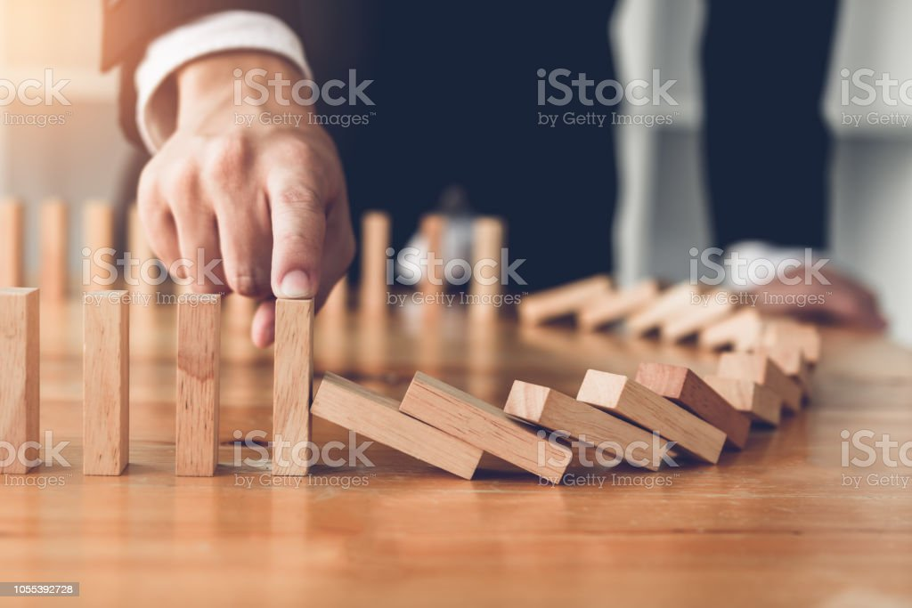 Close up finger businessman stopping wooden block from falling in the line of domino with risk concept. royalty-free stock photo