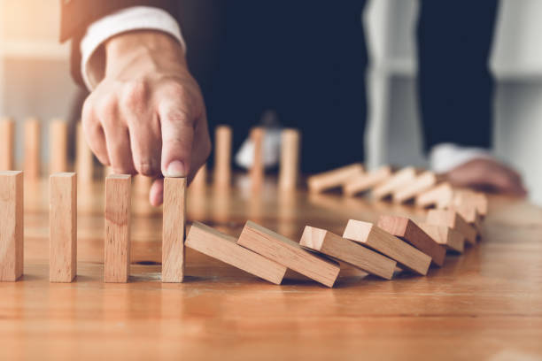close up finger businessman stopping wooden block from falling in the line of domino with risk concept. - rischio foto e immagini stock