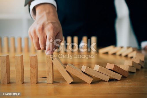 istock Close up finger businessman stopping wooden block from falling in the line of domino with risk concept. 1148423898
