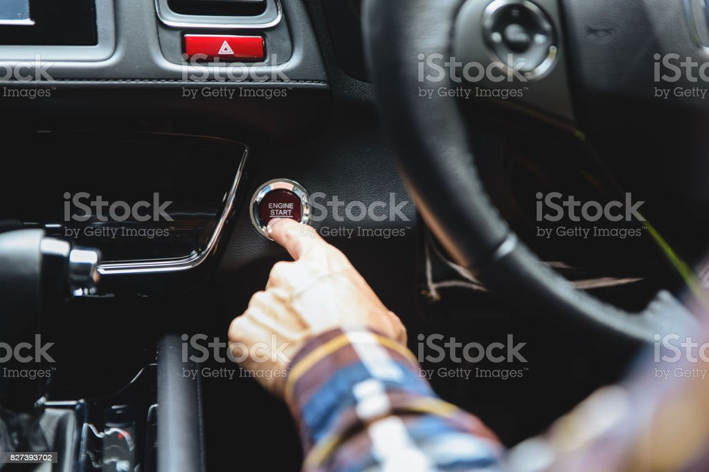 Close up Finger press button functions car engine start and stop in motor vehicle for pre start checklist concept. stock photo