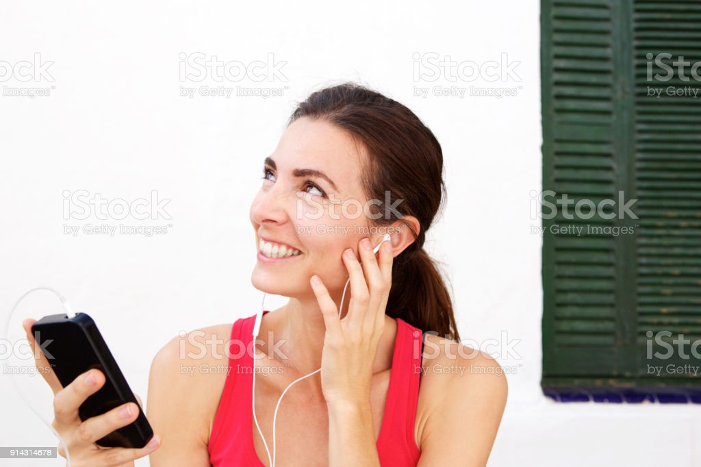 1c6301de Close up fit young woman relaxing with mobile phone and earphones after  workout session royalty-