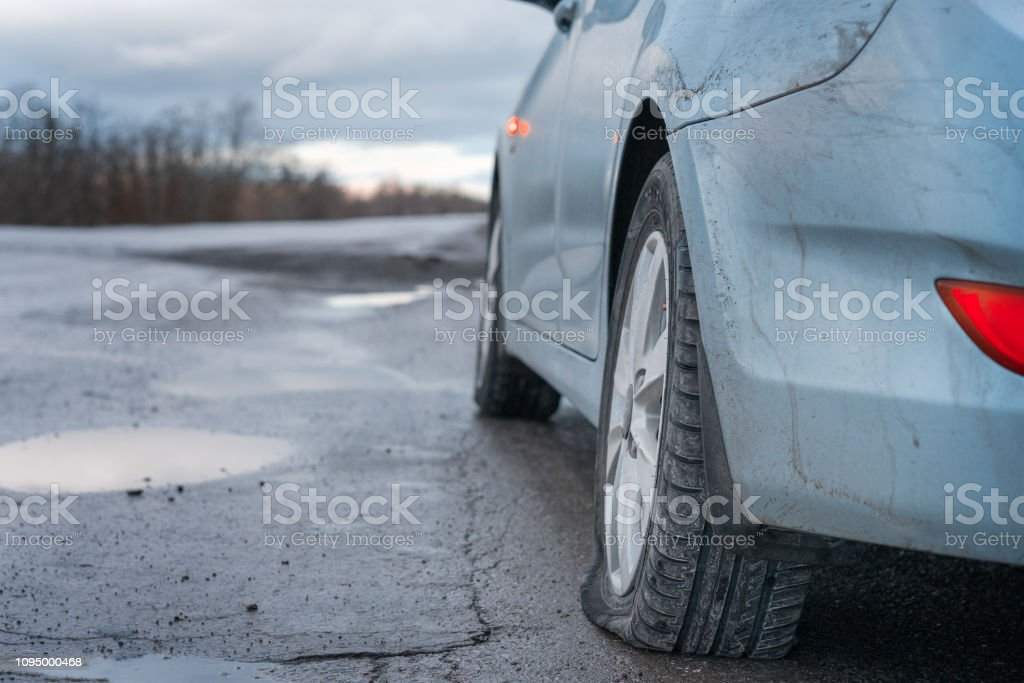Close up Flat tire and blue car on the road after the rain waiting for repair stock photo