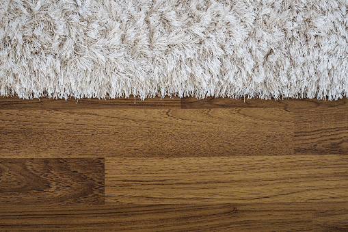Close up fluffy luxury carpet on laminate wood floor