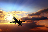 Transportation image of flying commercial passenger airplane over sunset sky and sunbeam