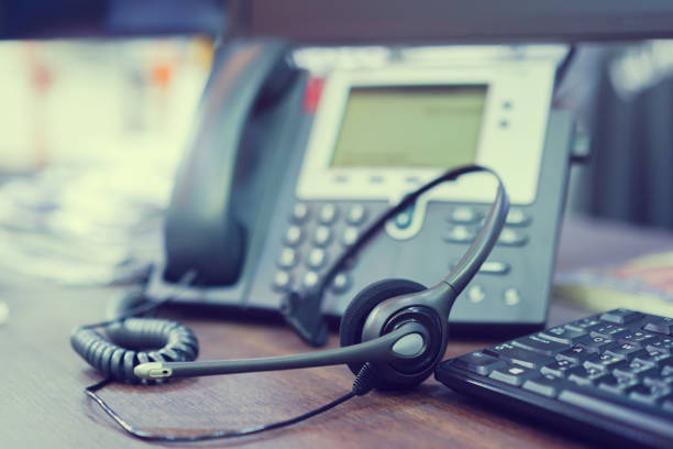 close up focus on call center headset device at telephone voip system at office desk for hotline telemarketing concept with vintage color filter - язык знаковая система стоковые фото и изображения