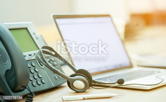 close up focus on call center headset device at telephone VOIP system at office desk for hotline telemarketing concept with vintage color filter