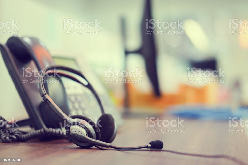 close up focus on call center headset device  headset VOIP system with telephone answer machine technology at operation office desk for hotline telemarketing and network operator concept stock photo