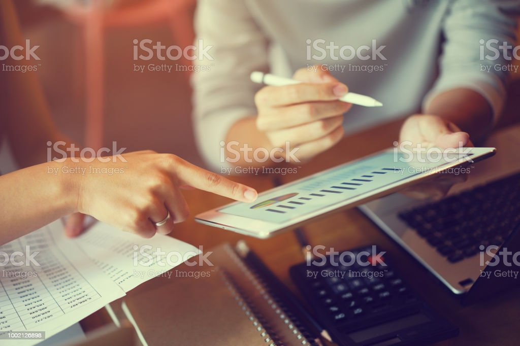 Close up focus on employee hand point review on dashboard tablet for ask and consulting about financial profit chart with partner at meeting company , teamwork concept royalty-free stock photo