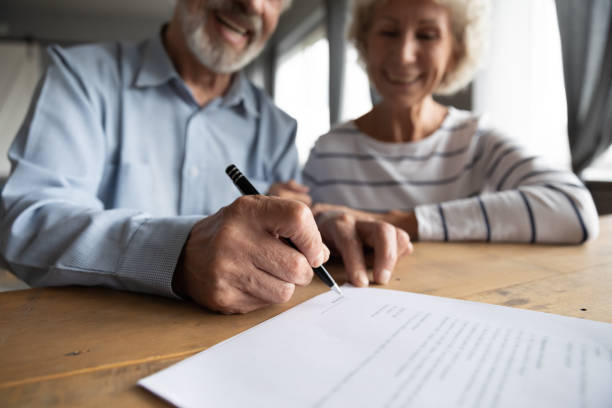Close up focus on wrinkled male hand signing paper document. Close up focus on wrinkled male hand signing paper document. Smiling elderly mature family couple putting signature on leasing or medical insurance contract, purchase agreement with real estate agent mortgages and loans stock pictures, royalty-free photos & images