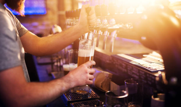 close up focus view of waiter pouring draft beer in the sunny bar. - beer pour stock photos and pictures