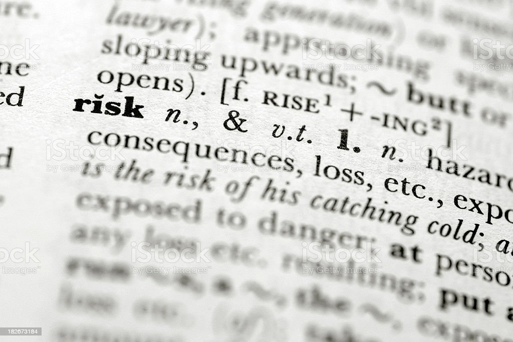 A close up focused on the definition of risk in a book stock photo