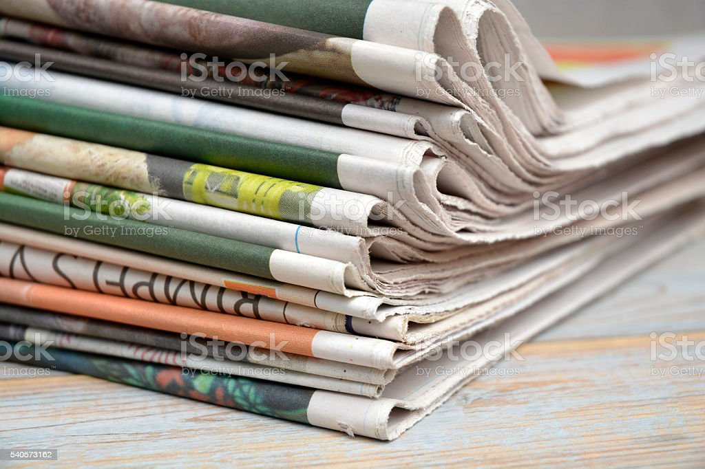 Close up of folded stacked color newspapers on grey wooden table...