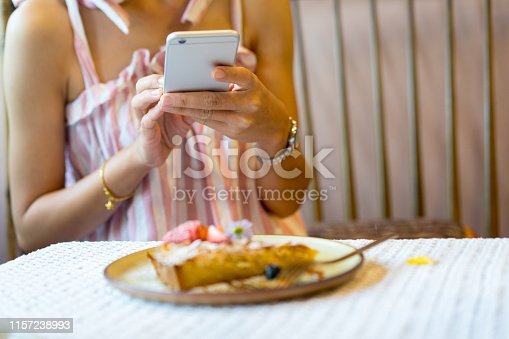 close up food blogger woman using smartphone for snap or take a photo of beauty homemade cake decor with strawberry on plate at coffee shop in relaxing weekend , and content creator lifestyle job  concept