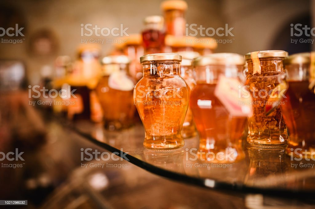 Close up food image of natural honey in little jar on shell on the market. Sunny warm trend toning photo stock photo