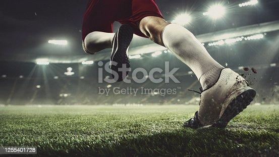 Leader. Close up football player at stadium in flashlight. Young sportsman during the match. Moment of attacking, catching. Concept of sport, competition, winning, action, motion, overcoming.