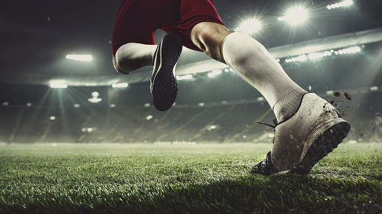 Close up football or soccer player at stadium in flashlights - motion, action, activity concept