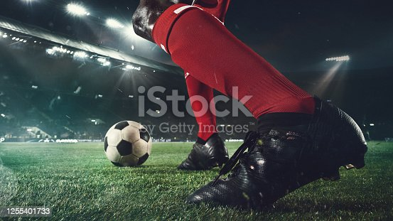 Emotions. Close up football player at stadium in flashlight. Young sportsman during the match. Moment of attacking, catching. Concept of sport, competition, winning, action, motion, overcoming.