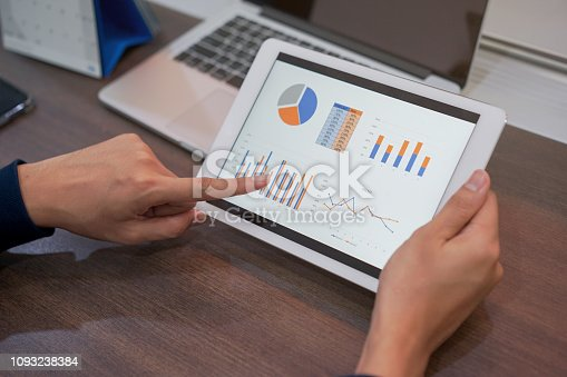 913603748 istock photo close up freelance man hand using by pointing on tablet screen dashboard summary of business marketing stock exchange graph and chart for check trend of globalization , financial news and index of trading , business and technology concept 1093238384