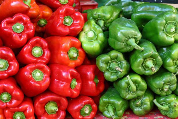 frische grüne und rote paprika hautnah - grüne paprikaschoten stock-fotos und bilder