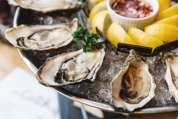 close up fresh oysters and many kinds of fresh oysters served in round tray with slice lemon and spicy sauce. - oyster stock pictures, royalty-free photos & images