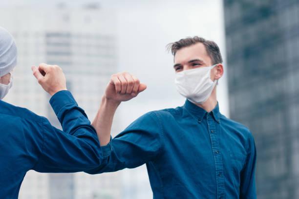 aus nächster Nähe. Freunde in Schutzmasken grüßen sich gegenseitig – Foto