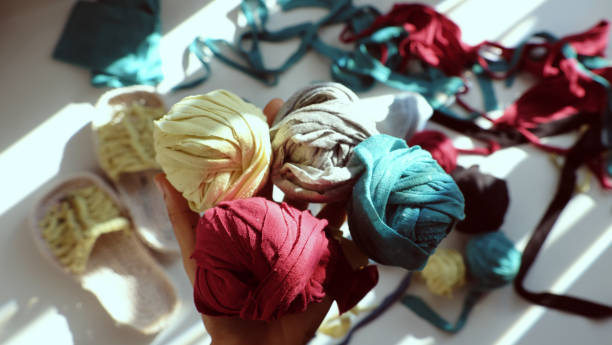 Close up from top view woman hand hold group colorful ball of yarn from recycle old t shirt stock photo