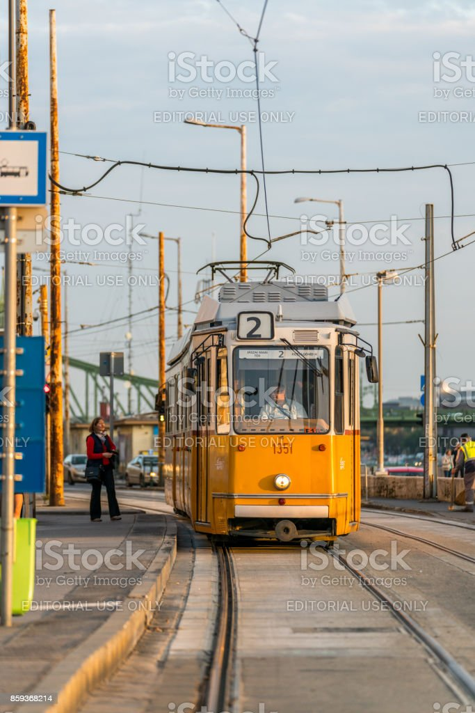 Close up front view of a yellow tram approaching a tram stop in Budapest Hungary to pick up passengers. royalty-free stock photo