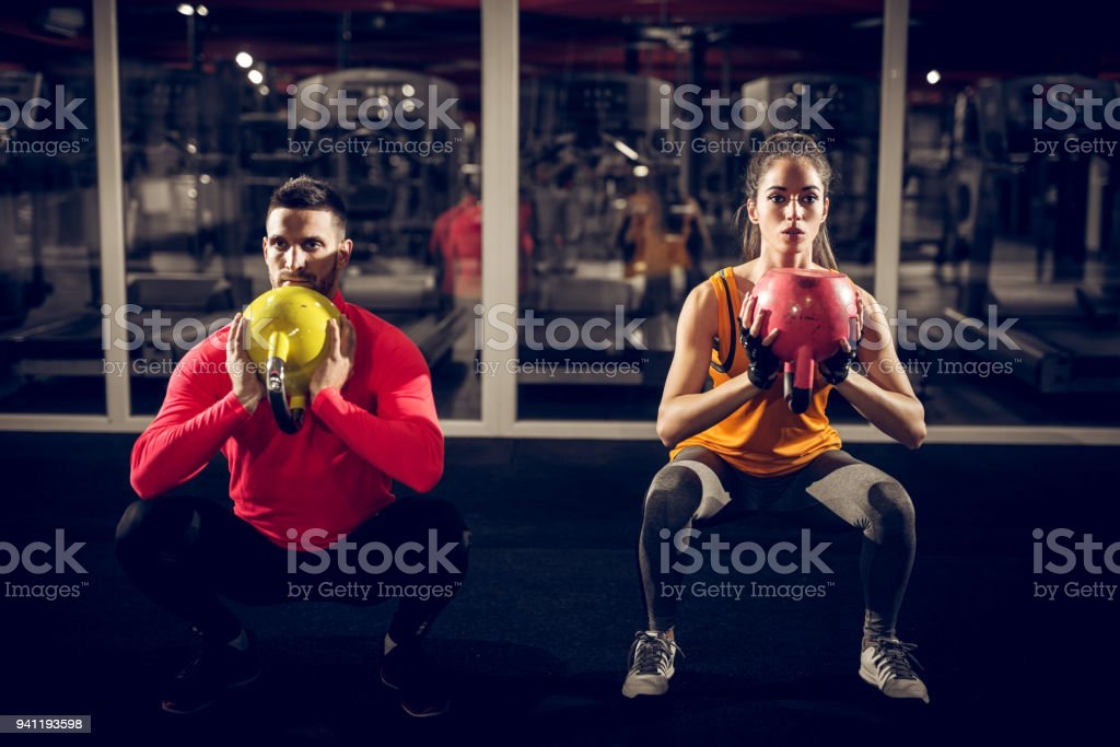 Close up front view of focused and motivated strong young fitness couple in sportswear crouching with the kettlebells reversed and doing squats in the gym at night. stock photo