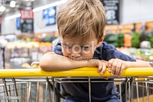 Close up frustrated Caucasian Child boy looking away sitting in a shopping cart