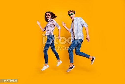 Close up full length body size photo of pair in summer specs he him his she her lady boy make dance moves jumping high fooling around wearing casual plaid shirt outfit isolated on yellow background.