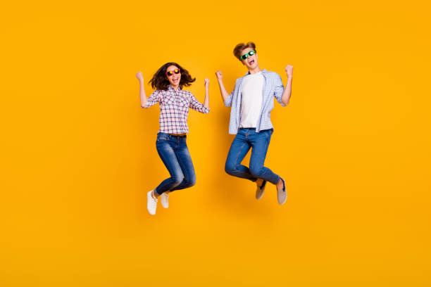 Close up full length body size photo of pair in summer specs he him his she her lady boy jumping high in greatness funny go travelling wearing casual plaid shirt outfit isolated on yellow background Close up full length body size photo of pair in summer specs he him his she her lady boy jumping high in greatness funny go travelling wearing casual plaid shirt outfit isolated on yellow background. jump shot stock pictures, royalty-free photos & images