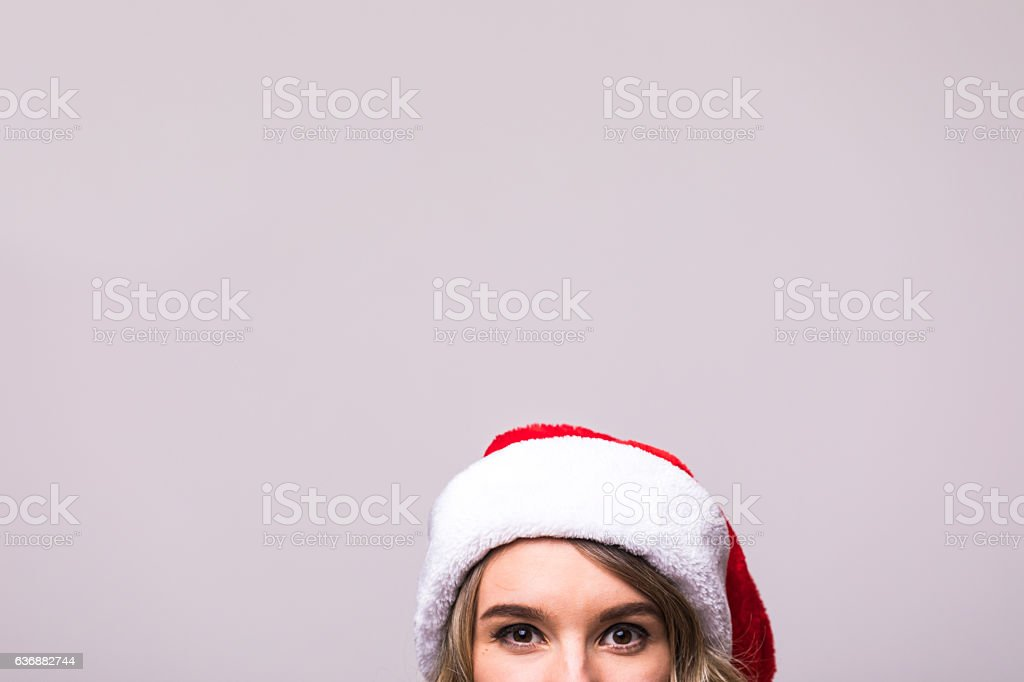 50140260f8710 Close up girls eyes in Christmas Santa hat isolated royalty-free stock photo