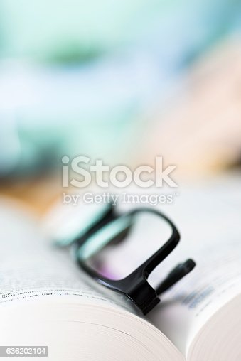 istock Close up glasses and open book 636202104