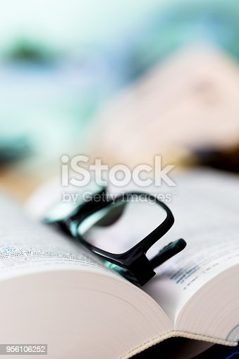istock Close up glasses and open book 956106252