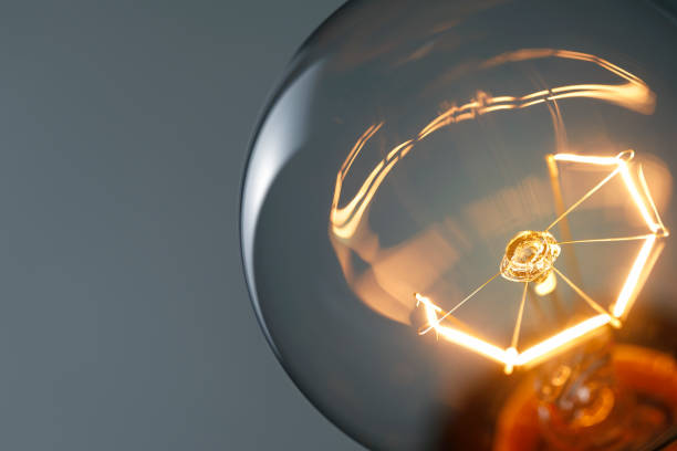 close up glowing light bulb - light bulb stock pictures, royalty-free photos & images