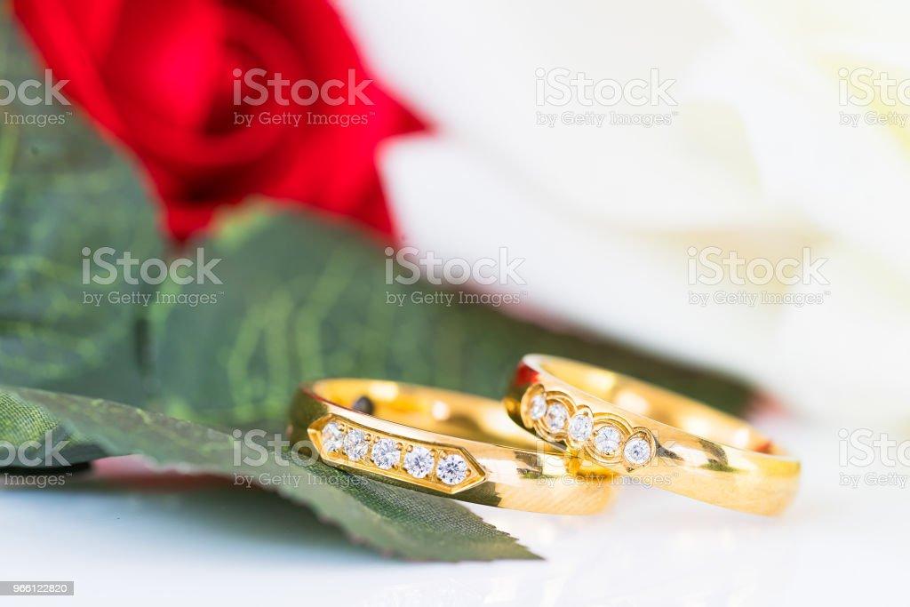 Stäng upp guld ring och röda rosor på vit - Royaltyfri Alla hjärtans dag Bildbanksbilder