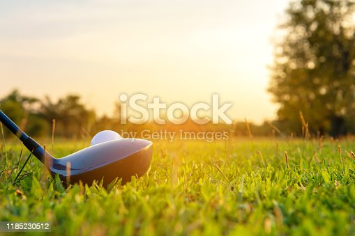 Close up golf ball and driver, player doing golf swing tee off on the green sunset evening time, presumably does exercise.  Healthy and Lifestyle Concept.