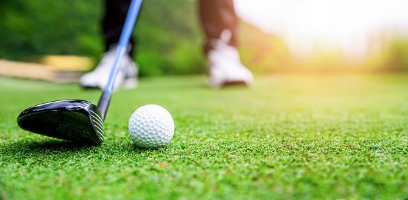 Close up golf ball on green grass field. sport golf club