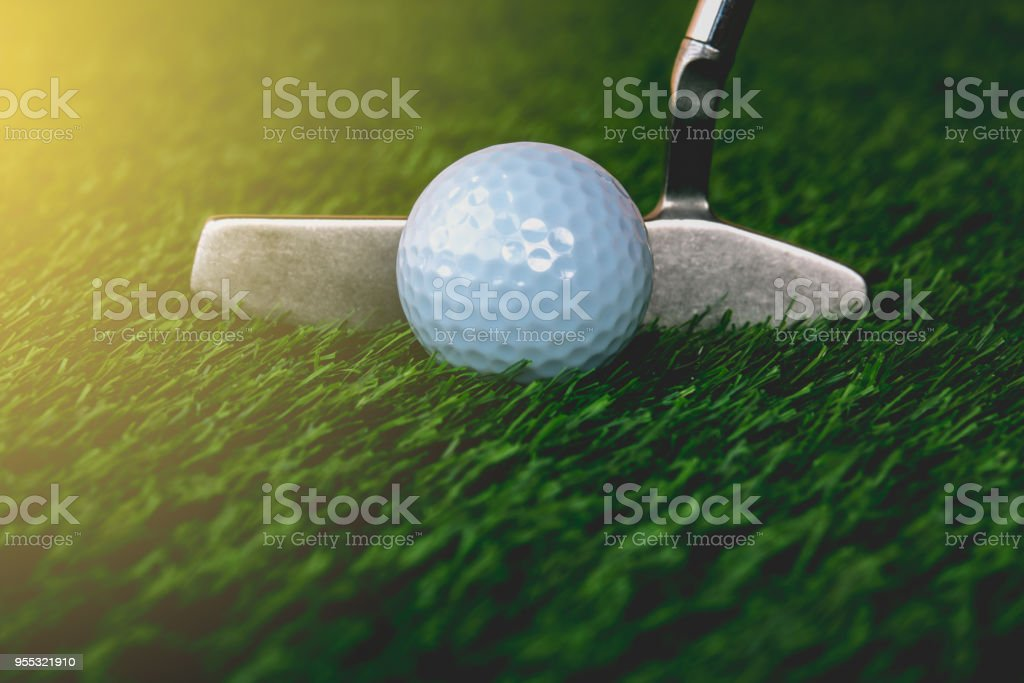 Close up golf club putting golf ball to hole