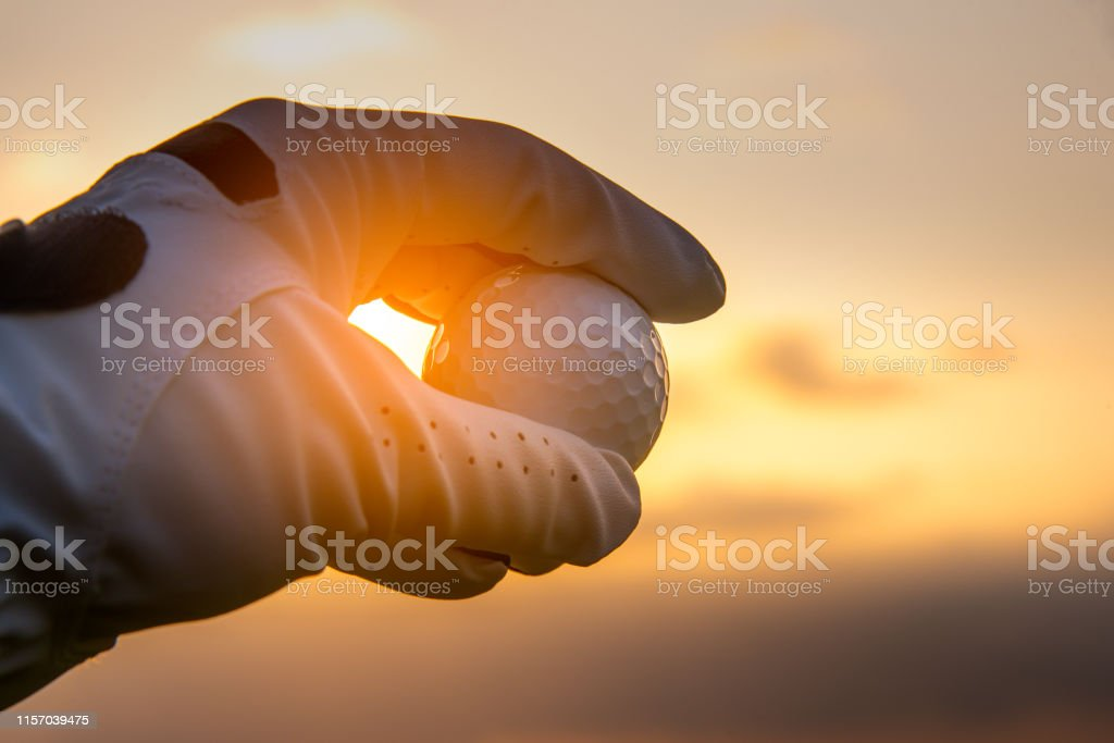 Close up golf player holding golf ball on white golf glove with...