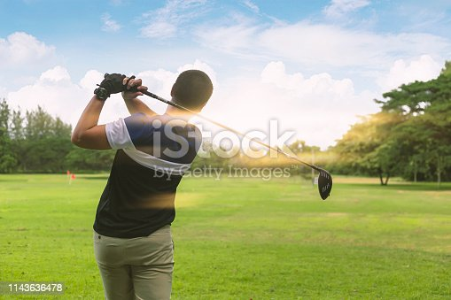 Close up Golfer is driving golf ball to green course with light flare.