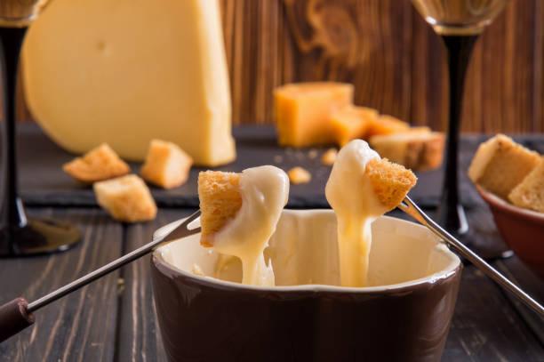 hautnah. schweizer fondue gourmet-dinner an einem winterabend mit verschiedene käsesorten auf einer tafel neben einem beheizten topf mit käse-fondue mit zwei gabeln dippen brot und weißwein. - fondue stock-fotos und bilder