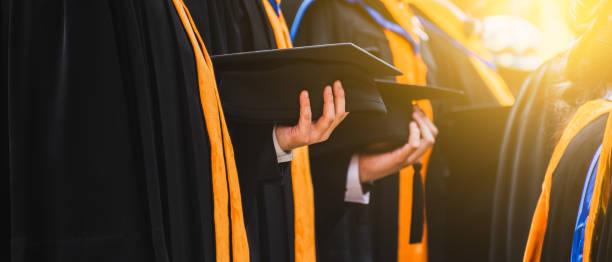 bouchent diplômé titulaire d'un chapeau. enseignement du concept succès en université. - remise de diplôme photos et images de collection