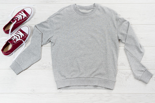 Close up gray blank template sweatshirt hoodie with copy space. Top view mockup pullover on white wooden background. Casual outfit. Flat lay template clothes.