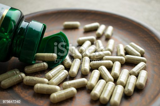 Close up Green capsules ginkgo biloba, bottle on clay brown plate on a burlap background. Dietary supplements for healthy  brain, memory. Vitamins and minerals for vegans and vegetarians. Superfood