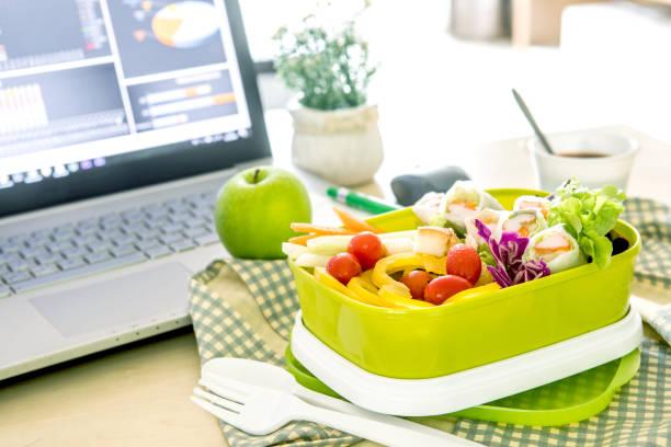 Großaufnahme grüner Lunch-Box am Arbeitsplatz der Arbeitstisch, gesunde Essgewohnheiten saubere Lebensmittel für die Ernährung und medizinische Versorgung-Konzept – Foto