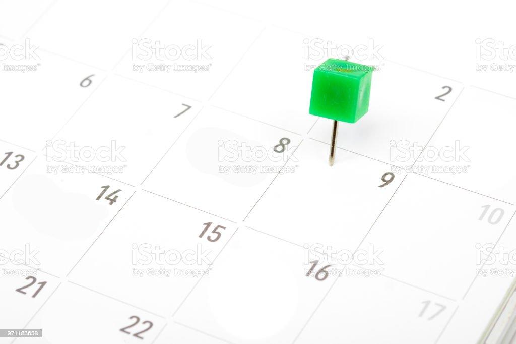 Close up green pin on White Calendar. stock photo